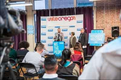 A crowd observes a press conference at Unite Oregon