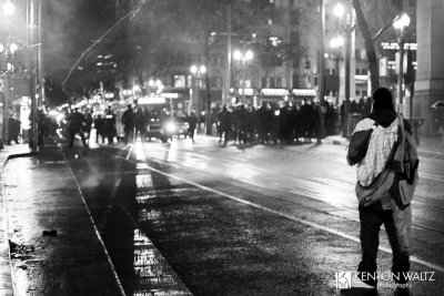 A protestor stands in the foreground, facing a line of police in riot gear about 10 yards away