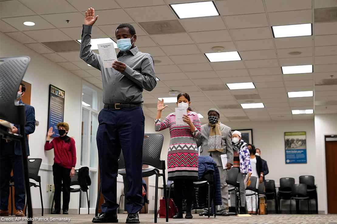 Candidates for American citizenship recite the Oath of Allegiance during a naturalization ceremony.