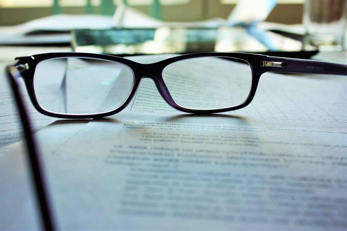 A pair of reading glasses rests on a document, whose content is indistinguishable