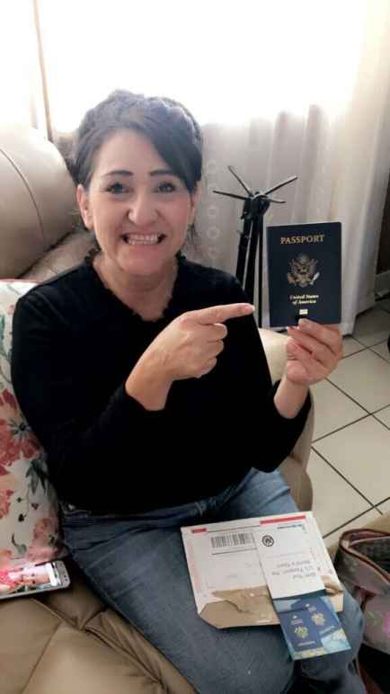 Maria Soto holds her passport and points to it