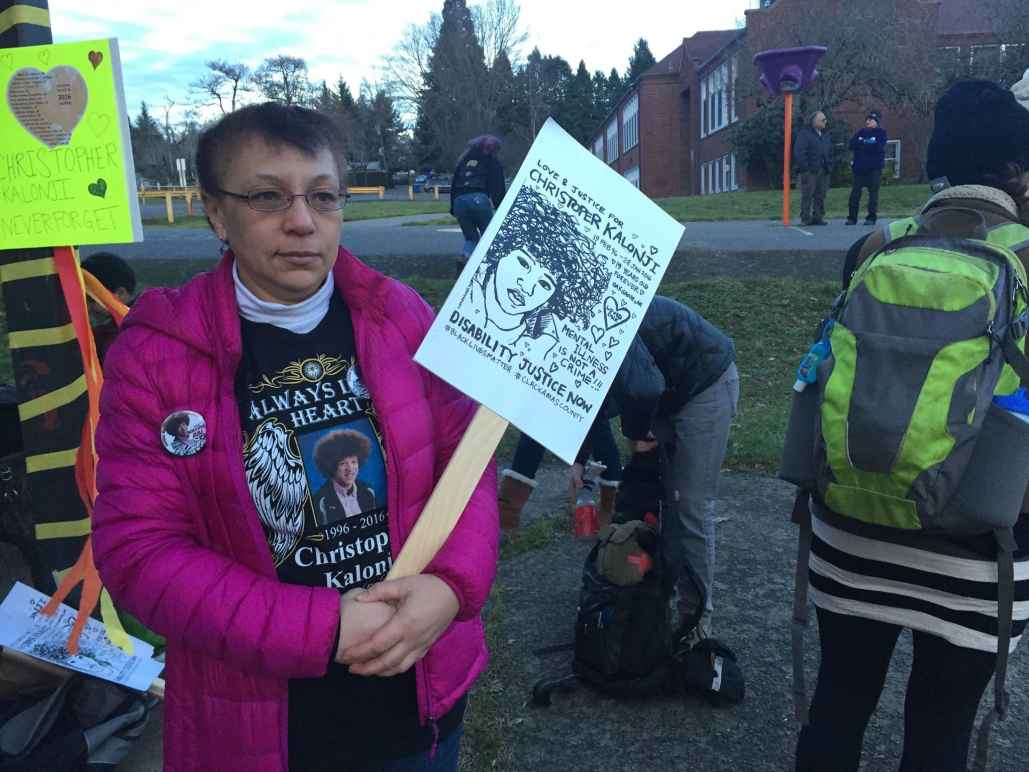Irene Kalonji holds a sign with her son's face on it at a memorial event