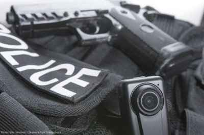 A close-up of sash reading 'Police', along with a body camera and handgun